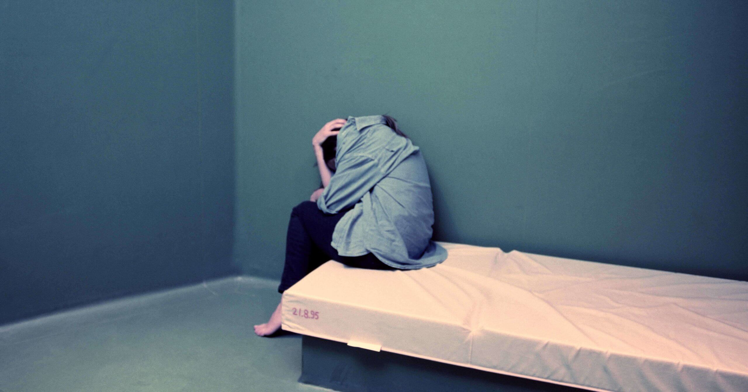 A depressed girl is curled up on the edge of a bed in a health care facility.